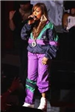 Singer Mariah Carey in multi-colored windbreaker jumpsuit on stage behind a microphone